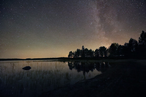 Photo shows the Milky Way and the bright reflection of the planet Mars on lake Korpijarvi at Villa Cone Beach.