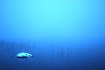 Photo shows a snowy piece of rock in the lake under foggy morning at Villa Cone Beach.