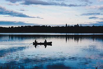 Photo shows two people in a boat on a midnight lake.