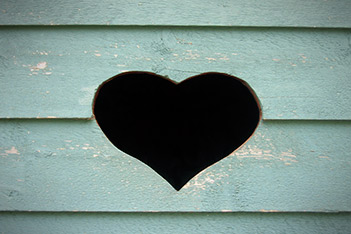 Photo shows a heart figure cut in the wall of a wooden building, as a symbol of friendship and love.