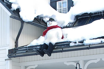Photo shows a young daredevil snow man sitting at the edge of Villa Cone Beach roof.