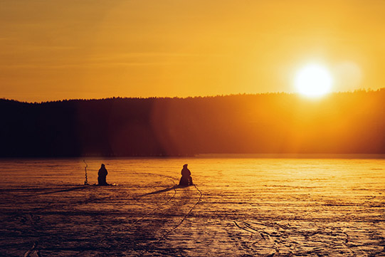 Photo shows two men ice fishing on a lake ice and the Sun shining just above the horizon in the daytime.