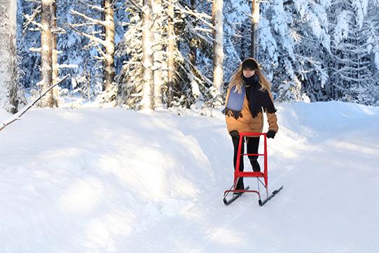 Photo shows a young woman kicksledding on a snowy Villa Cone Beach road.
