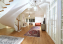 Photo shows Villa Cone Beach living room, antique oriental carpets and the curved stairs up to the bedrooms.