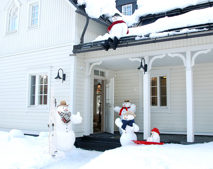 Photo shows a snow man family welcoming Villa Cone Beach guests for friendly luxury holiday.
